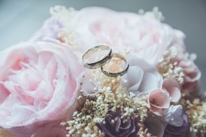 Featured Image: bridal bouquet of pink roses with the bride and groom's wedding bands laying on top of it