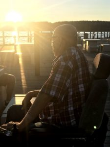 Elderly man wearing oxygen, watching the sunset over the lake from his power wheelchar